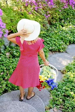 Photo of a woman in a red dress with a white hat walking down a stone path through a flower garden